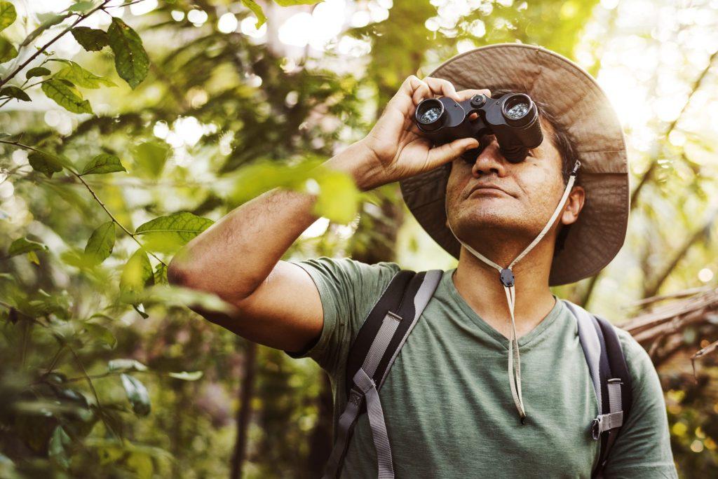 hombrecon prismaticos observando aves